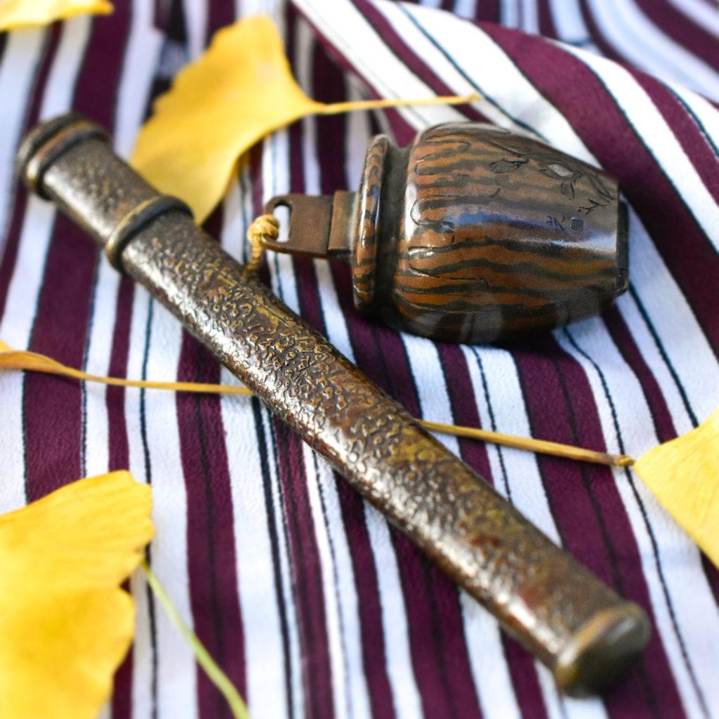 木目金矢立(やたて)江戸時代の筆記具の事です。木目金によってつくられたつぼ型の黒壺は珍しく、筆入れは真鍮地に荒らし鏨で表情をつけたもの。